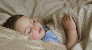 Portrait of toddler child,  boy or gir, sleeping under a blanket in a bed.