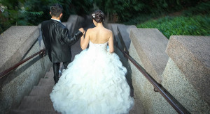 A rear view of newlyweds holding hands and walking down the stone steps.